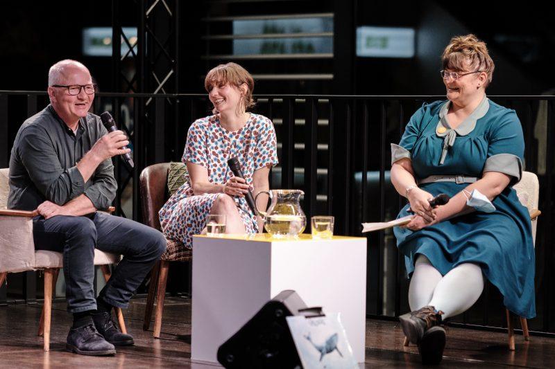 Drei Personen im Gespräch auf einer Bühne
